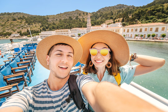 Happy couple in love taking selfie on a deck of a sea cruise ship wearing hats. Vacation and travel concept