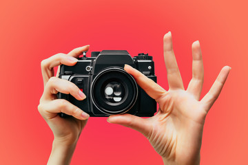 Vintage Camera in female hand. A photo. Photographer. Manual focus. Colored background. Red