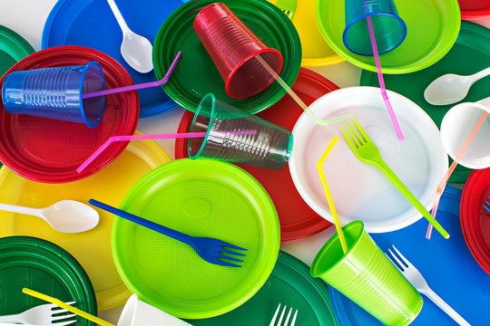 Bright color disposable plastic tableware  background. Picnic set. Ecology problem. Top view.