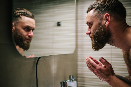 Young bearded hipster man washing his face with water in the bathroom while looking himself in the mirror.