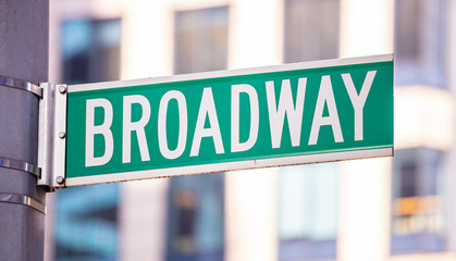 Fototapete - Broadway road sign. Blur buildings facade background, Manhattan downtown