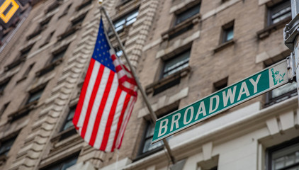 Wall Mural - Broadway road sign. Blur American flag and buildings facade background, Manhattan downtown