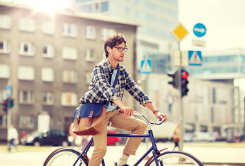 people, style, leisure and lifestyle - young hipster man with shoulder bag and earphones riding fixed gear bike on city street Fototapete