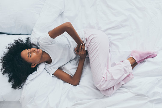 top view of pretty african american woman suffering from abdominal pain while lying on white bedding with closed eyes