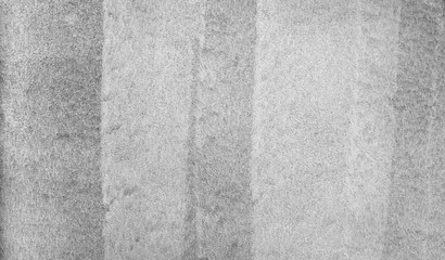 Texture of light grey and white vertical stripes painted as undercoat on a concrete wall.
