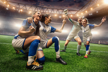 Fototapeta Happy Female Soccer players on a professional soccer stadium. Girls Team emotionally celebrates victory