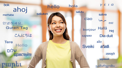 translation, education and people concept - happy asian young woman looking up over greeting words in different foreign languages
