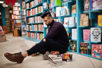 Tall smart arab student man, wear on violet turtleneck and eyeglasses, at library sitting against books shelves.