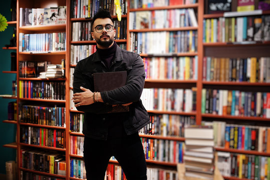 Tall smart arab student man, wear on black jeans jacket and eyeglasses, at library with book at hands.