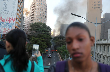 Women take pictures of burning tyres blocking the street, during a general strike against the government's pension plan in downtown Sao Paulo