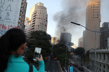 A woman takes picture of burning tyres blocking the street, during a general strike against the government's pension plan in downtown Sao Paulo
