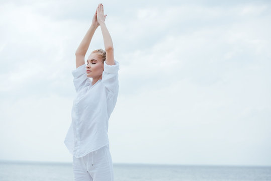 attractive girl with closed eyes practicing yoga and standing with praying hands
