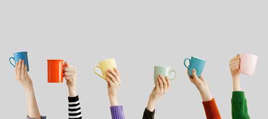 Many different arms raised up holding coffee cup Wall mural