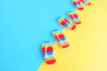 pattern made with colorful summer flip flops toys shoes on bright blue yellow background top view toned. Minimal summer concept. Copy space
