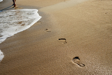 Beach, wave and footprints - woman walking barefoot leaving footsteps in sand