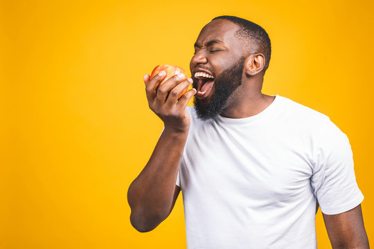Healthy african american man holding an apple isolated against yellow background.