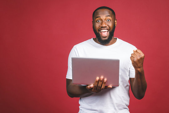 Excited happy afro american man looking at laptop computer screen and celebrating the win isolated over red background.