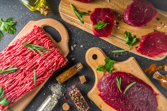 Different raw steak and minced beef meat with herbs and spices for cooking, black concrete or stone table