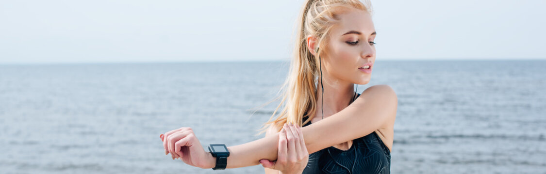 panoramic shot of beautiful athletic girl stretching and listening music near sea