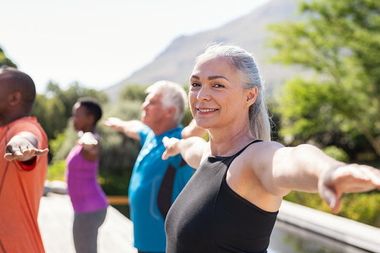 Senior woman stretching arms in yoga class