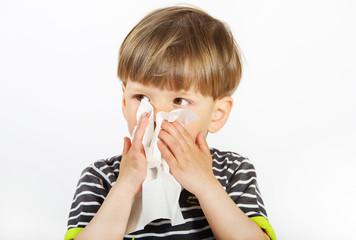 Ein dreijähriger Junge putzt sich sie Nase