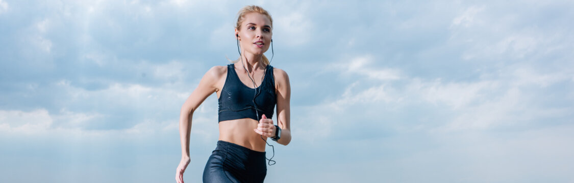 panoramic shot of sportive blonde woman running and listening music in earphones