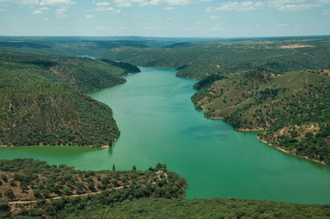 Tagus River running through a hilly valley with trees and house