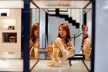 A woman looks at a luxury shop window in Hong Kong