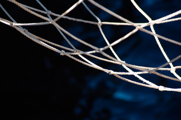 Fishing net and blue dark water surface, soft focus
