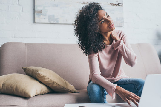beautiful african american woman suffering from neck pain while sitting on sofa near table with laptop