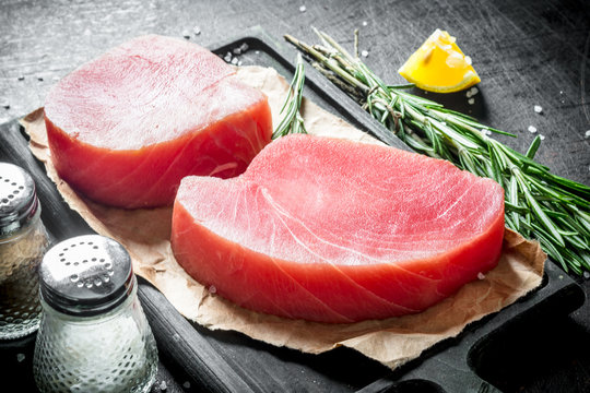Raw tuna steak on a cutting Board with paper.