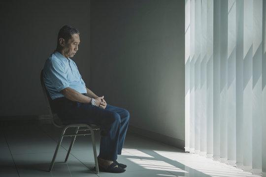 Lonely aged man looks sad near the window