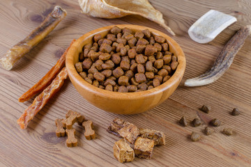 dried dog food in a bowl and different snack, chicken filet, antlers, lung, ear on wooden background
