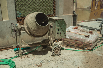 Cement mixer with hose and cement bags in a construction site
