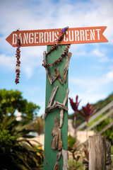 A Dangerous current sign with dried leis at Waimea Beach.
