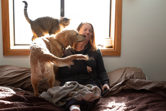 Woman getting loved by cat and dog kisses
