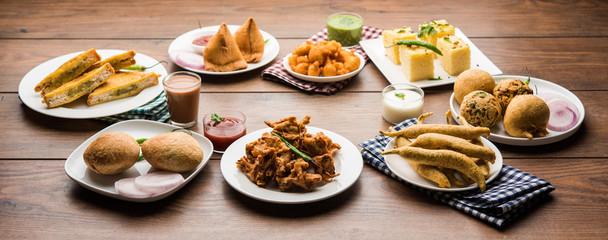 Indian Tea time snacks  in group includes Veg Samosa, Kachori/kachaudi, aloo bonda, khaman dhokla, bread, onion,chilli and moong pakora/pakoda/bhaji/bhajji/Bhajiya/bajji with sauces, selective focus