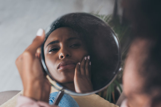 upset african american woman looking at mirror while suffering from jaw pain