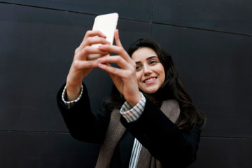 Young attractive woman taking picture of herself with a smartphone