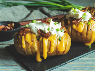 Fototapete - baked potato stuffed with cheese, bacon and sour cream. loaded hasselback potatoes