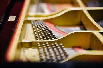 Detail of the interior of a piano with the soundboard, strings and pins.