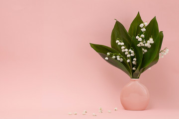 Bouquet of lily of the valley in a pink vase and white flowers of lily of the valley on a pink background