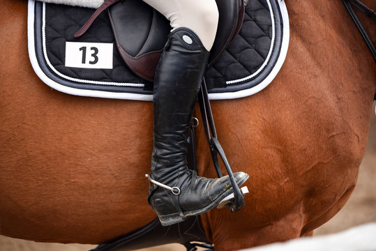 Rider with boots on horse at a show jumping competition