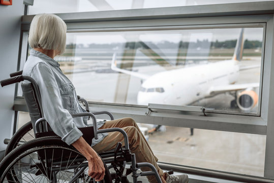 Cheerful mature lady on disabled carriage in airport