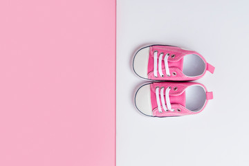 Cute pink baby girl sneakers close up on pink and white background