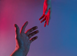 Obraz Two hands reach out to each other with a red-blue neon light. Minimalism fashion. Surrealism. Concept art - fototapety do salonu