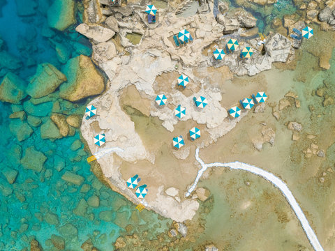 Aerial view of blue and white parasols on rocky coast