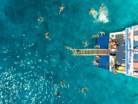 Aerial view of people on ferry diving into sea, Ithaki island, Greece