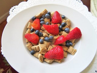 Bowl of cereal with fresh blueberries and strawberries for a nutritional breakfast