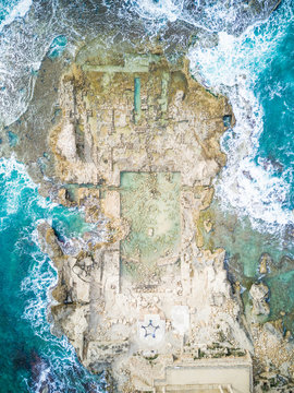 Aerial view of people drawing a star with their bodies on the rocks in the sea of Caesarea, Israel.